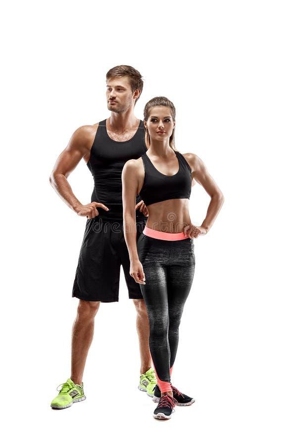 体育,健身,锻炼概念 适合的夫妇、坚强的肌肉摆在白色背景的男人和亭亭玉立的妇女 免版税库存照片