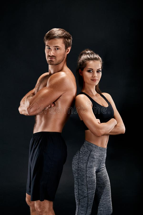 体育,健身,锻炼概念 适合的夫妇、坚强的肌肉摆在黑背景的男人和亭亭玉立的妇女 库存照片