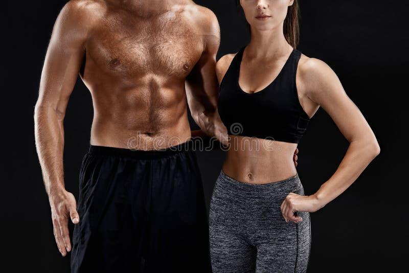 体育,健身,锻炼概念 适合的夫妇、坚强的肌肉摆在黑背景的男人和亭亭玉立的妇女 库存图片