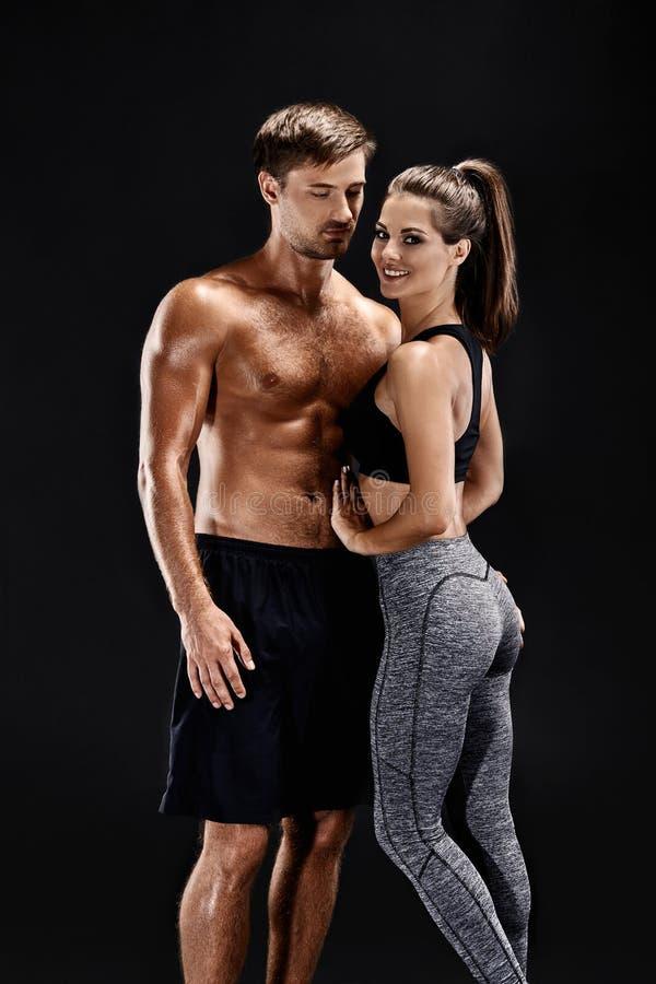 体育,健身,锻炼概念 适合的夫妇、坚强的肌肉摆在黑背景的男人和亭亭玉立的妇女 免版税图库摄影