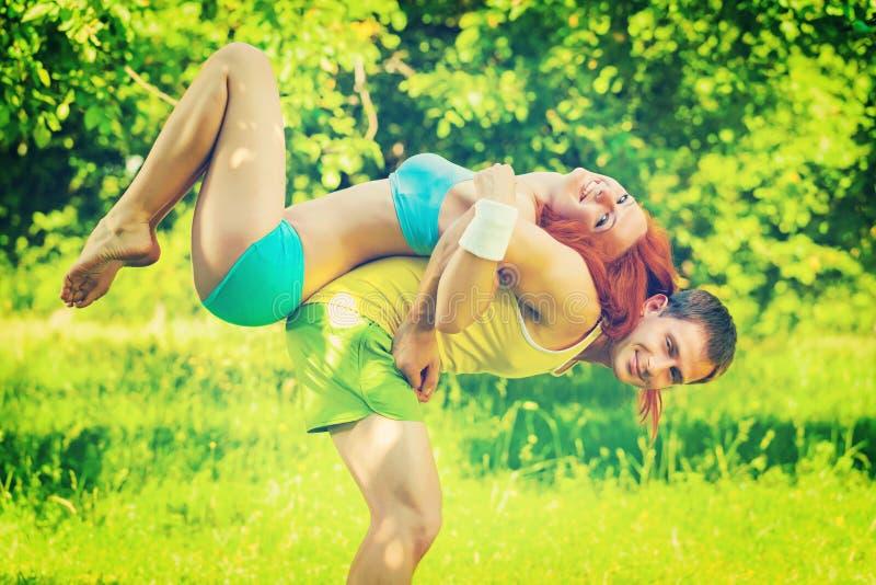 体育结合年轻使用在公园领域instagr的人和女孩 免版税库存图片