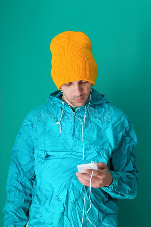 体育90s样式夹克和黄色帽子藏品智能手机的年轻人在蓝色背景 库存图片
