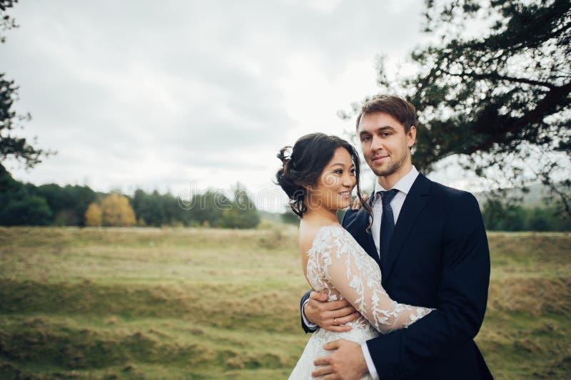体贴亲吻在云杉的树之间的最近被婚姻的夫妇 免版税图库摄影