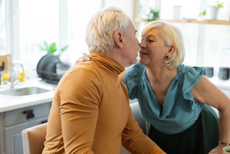体贴亲吻她年迈的灰发的丈夫的愉快的引诱的变老的配偶 免版税库存照片