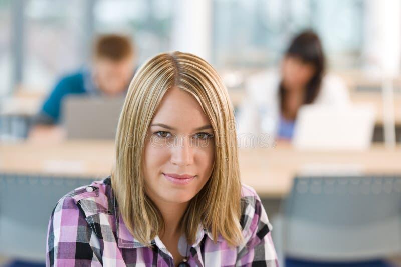 体贴教室的女学生 免版税库存图片