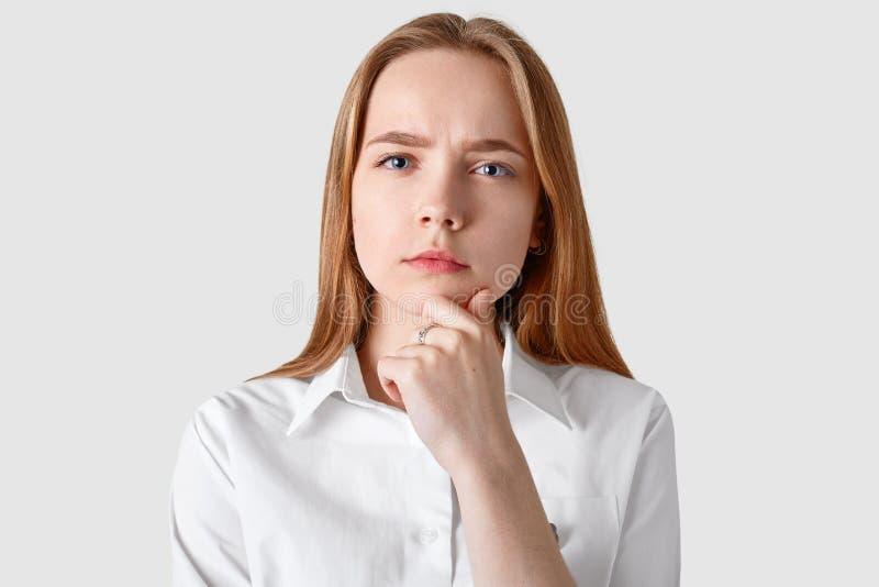 体贴的严肃的妇女,软的皮肤特写有蓝眼睛的,握下巴并且看直接地照相机,有长的直发, 免版税库存照片
