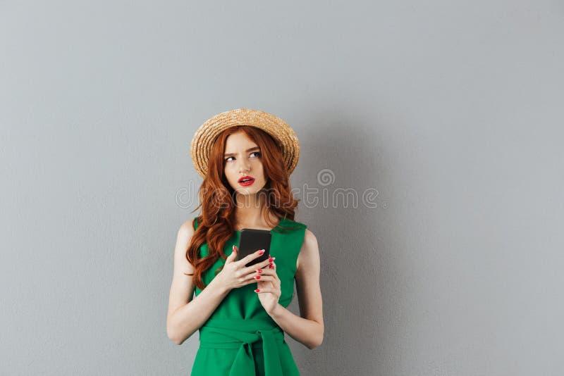 体贴的姜妇女佩带的草帽和绿色画象  免版税库存图片