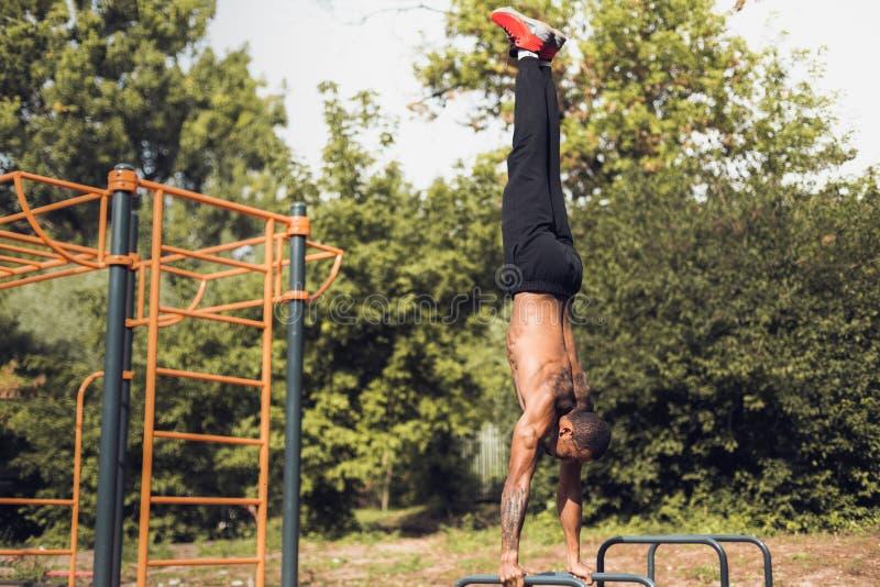 体重锻炼 站立在手上和做俯卧撑的人 免版税库存照片