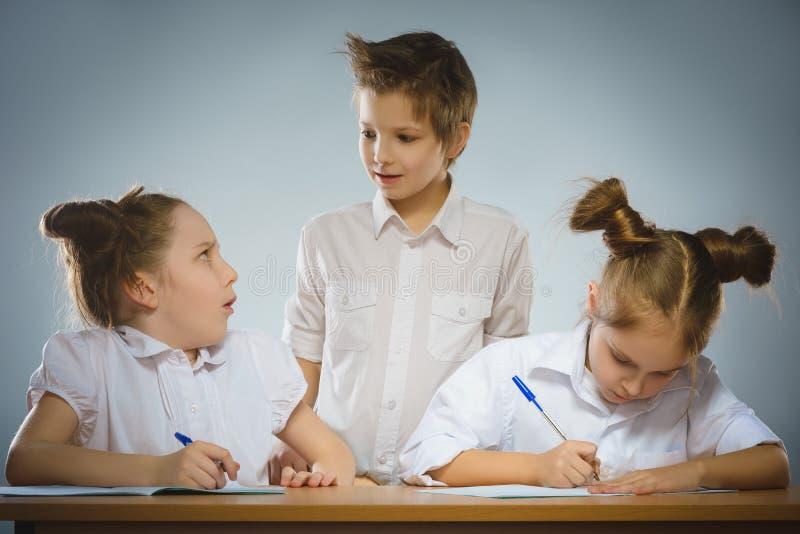 体贴的女孩和小男小学生灰色背景的 背景黑名册概念copyspace学校 免版税图库摄影