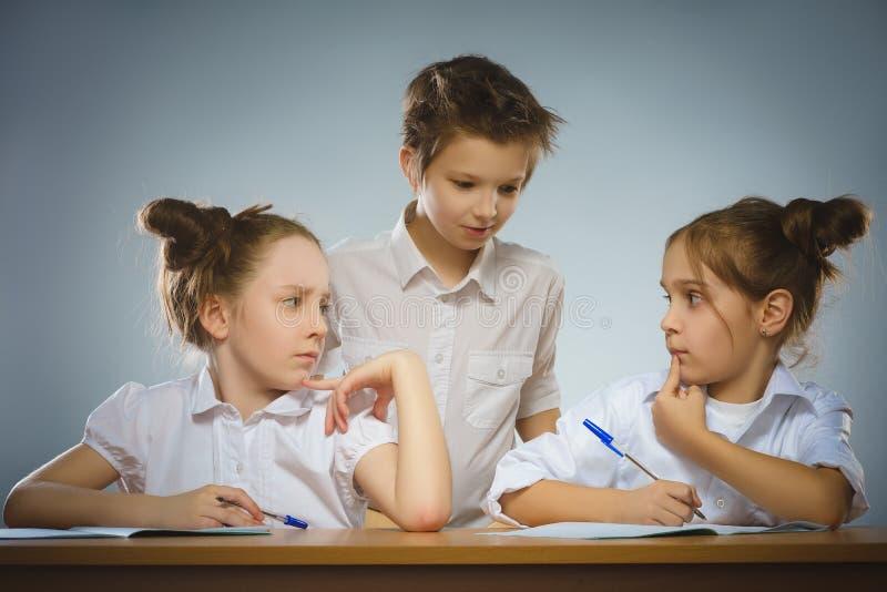 体贴的女孩和小男小学生灰色背景的 背景黑名册概念copyspace学校 免版税库存图片
