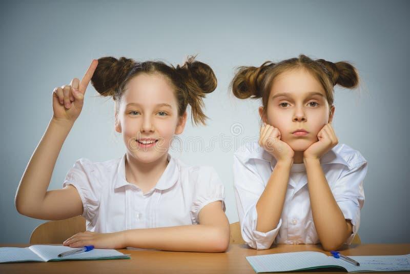 体贴的女孩和愉快的女孩在书桌坐灰色 背景黑名册概念copyspace学校 免版税库存照片