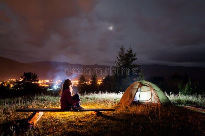 体贴的女孩坐长凳在帐篷和营火附近 免版税库存照片