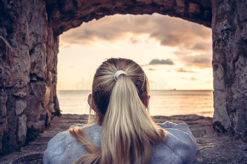 体贴的妇女致力入美好的日落的沉思在海的通过老城堡窗口与剧烈的天空和perspe的 免版税库存图片