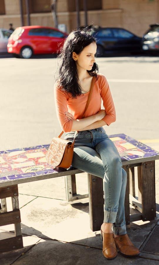 体贴的美丽的女孩下来坐街道长凳 免版税库存图片