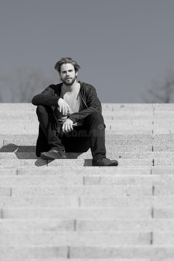 体贴的年轻人坐步反对蓝天背景 免版税库存图片