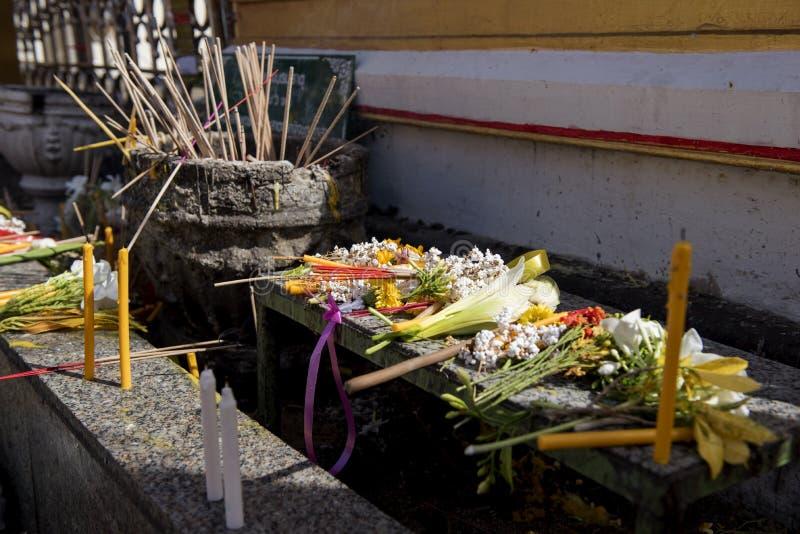 佛教人民投入花,香,蜡烛,并且在桌上的莲花以后为塔达,泰国祈祷 免版税图库摄影