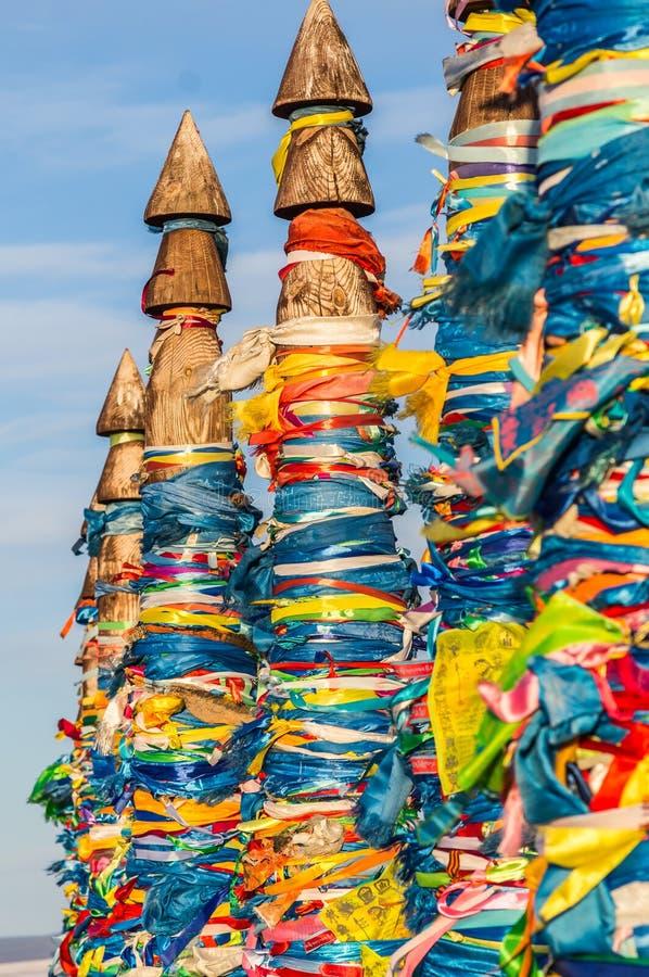 佛教僧人与色的丝带的柱子毛哔叽在海角Burhan,贝加尔湖,俄罗斯 免版税图库摄影