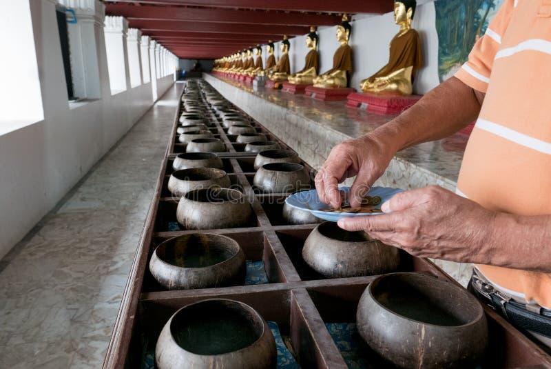 佛教徒捐赠金钱到寺庙由他们的信念和维护寺庙在泰国 库存照片