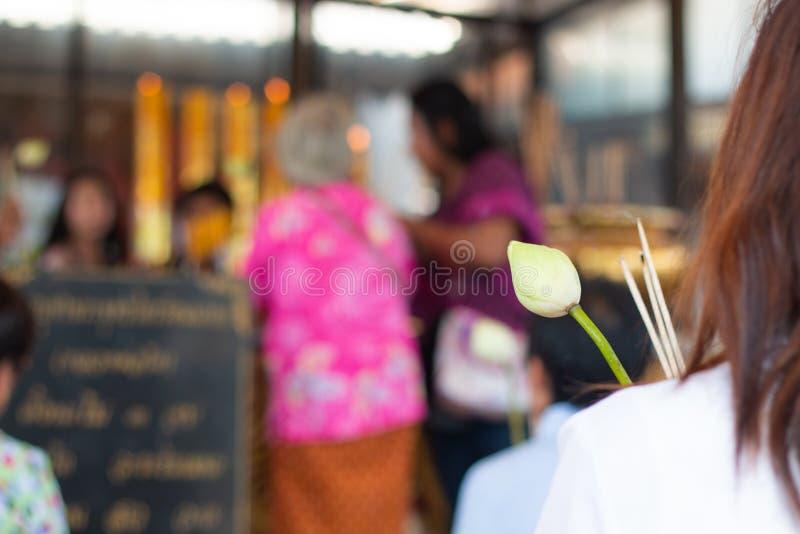 佛教徒祈祷并且崇拜与莲花和香火和被弄脏的寺庙背景 库存图片
