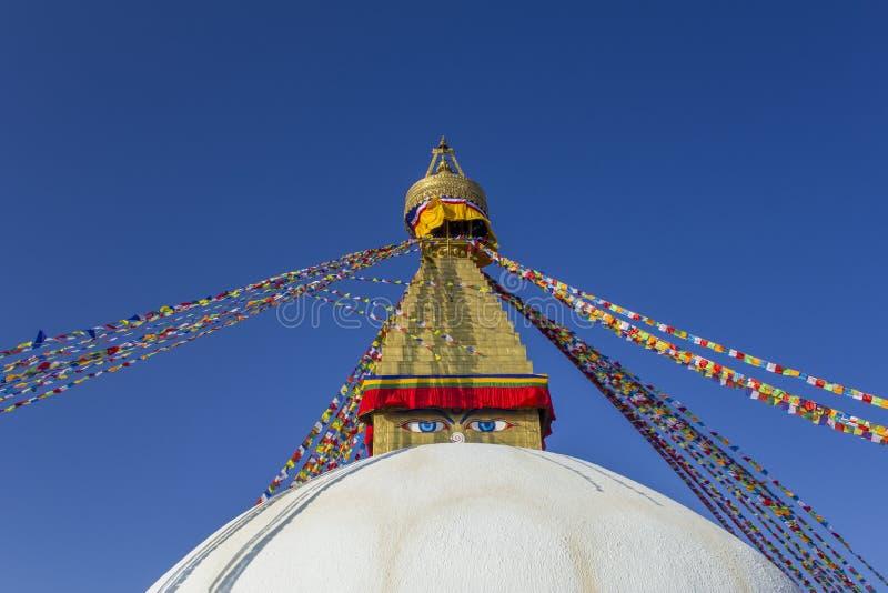 佛教西藏白色stupa寺庙Bodnath在有多彩多姿的祷告旗子的加德满都反对一干净的天空蔚蓝 库存图片