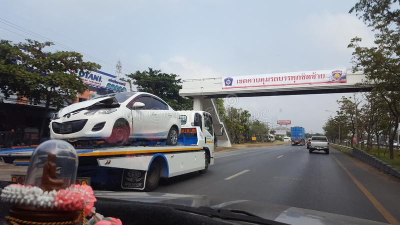 佛统,泰国- 12月29,2018:运载瑕疵汽车的拖车 在公路事故以后的马自达汽车 库存照片