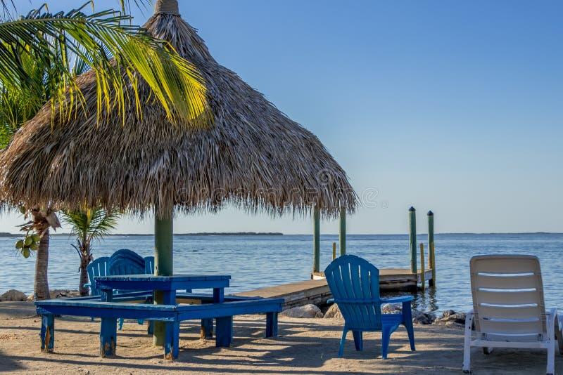 佛罗里达州基拉戈的沙滩椅和提基小屋 免版税库存照片