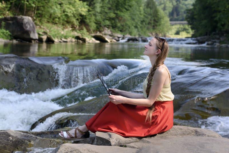 作一条红色裙子的美丽的长发女孩坐与与膝上型计算机在石头反对a小瀑布的背景  库存图片