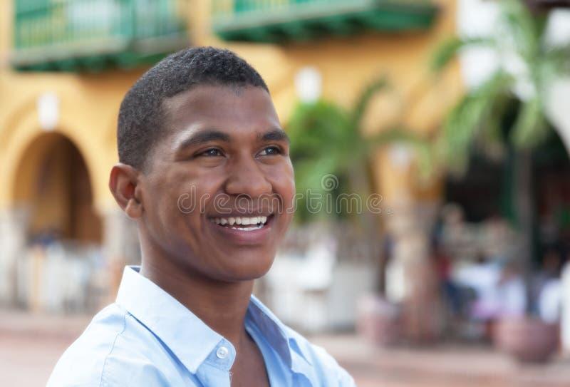 作一件蓝色衬衣的人在一个五颜六色的殖民地镇 免版税库存照片