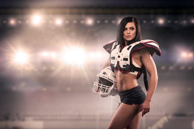 作为一名美国橄榄球运动员打扮的运动女性 实际统一,盔甲,填充,球 免版税图库摄影