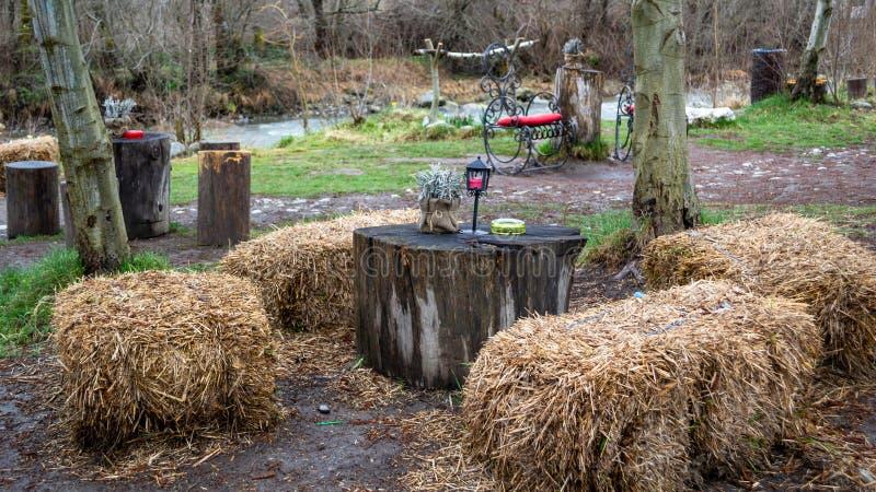 作为与树日志的椅子使用的干草堆作为桌,室外在农村特兰西瓦尼亚,罗马尼亚 野餐的概念在庭院里 图库摄影