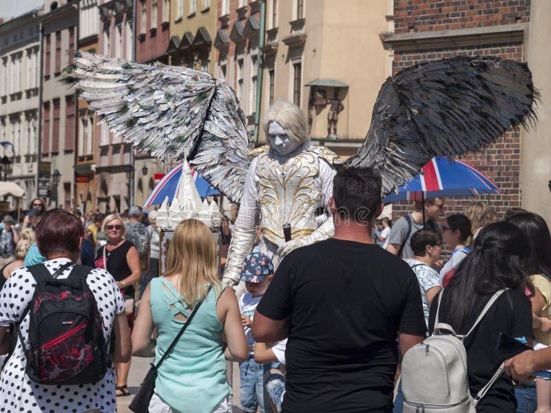 作为与的一个天使打扮的卖艺人/街道执行者巨大的翼,围拢他的人群等待拍照片 免版税库存照片