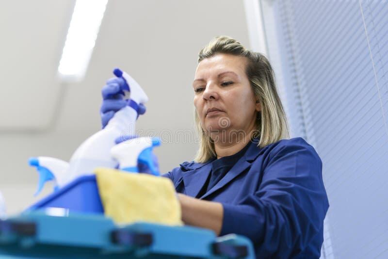 作为专业擦净剂的妇女工作在办公室 库存图片