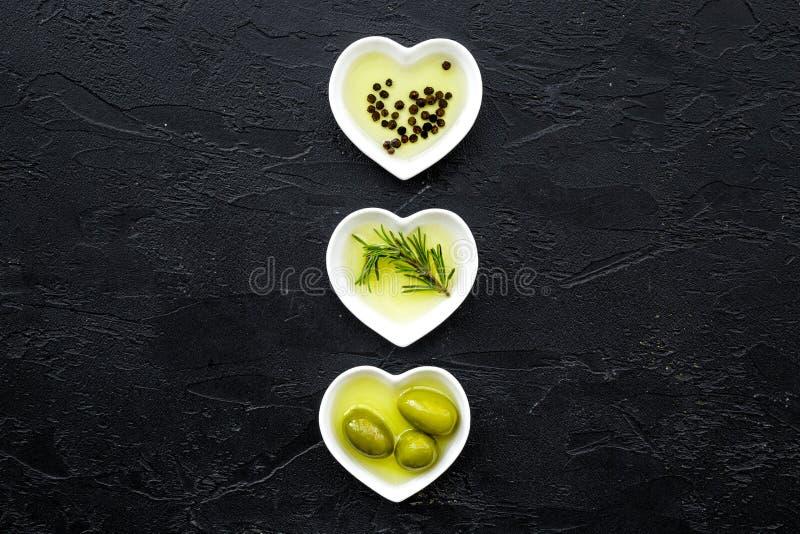 作为健康饮食产品的橄榄油 有橄榄油的心形的碗用里面绿橄榄、迷迭香和黑胡椒 免版税库存照片