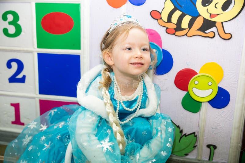 作为公主打扮的愉快的小女孩在新年的假日 库存图片