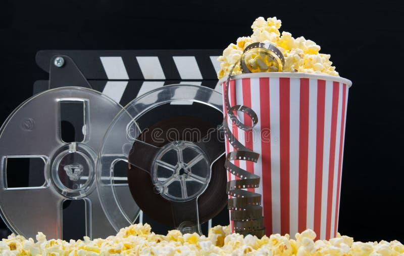 作为和快餐电影院、玉米花和两个桶的烤干酪辣味玉米片在黑背景 库存图片