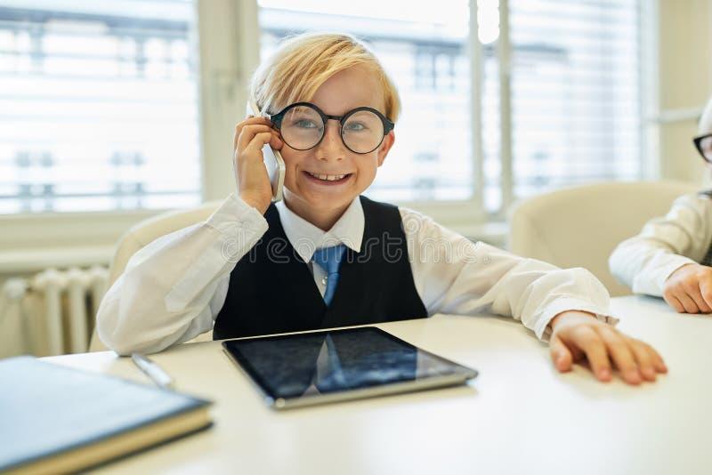 作为商人的孩子打电话与智能手机 库存图片