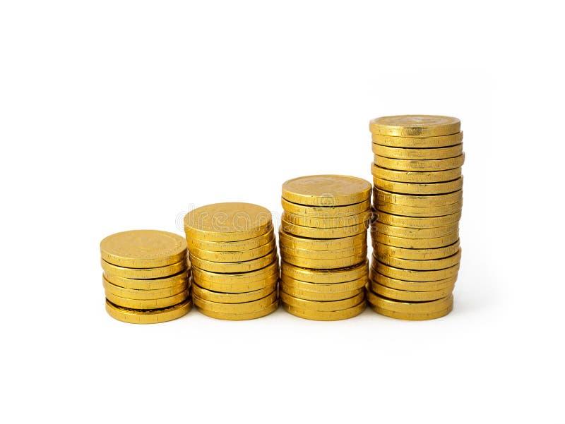 作为图表被安排的金黄硬币堆隔绝在白bg 免版税库存图片