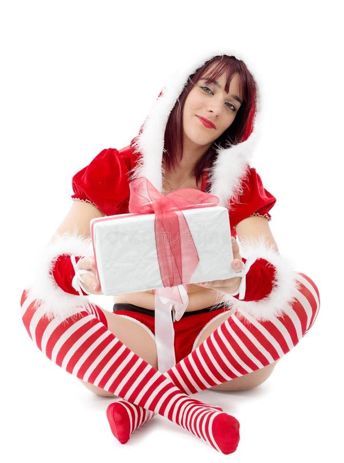 作为圣诞老人打扮的美丽的妇女坐与pres的地板 图库摄影