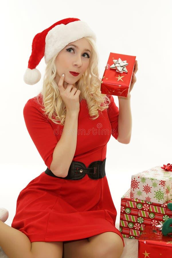 作为圣诞老人打扮的美丽的妇女,拿着礼物 图库摄影