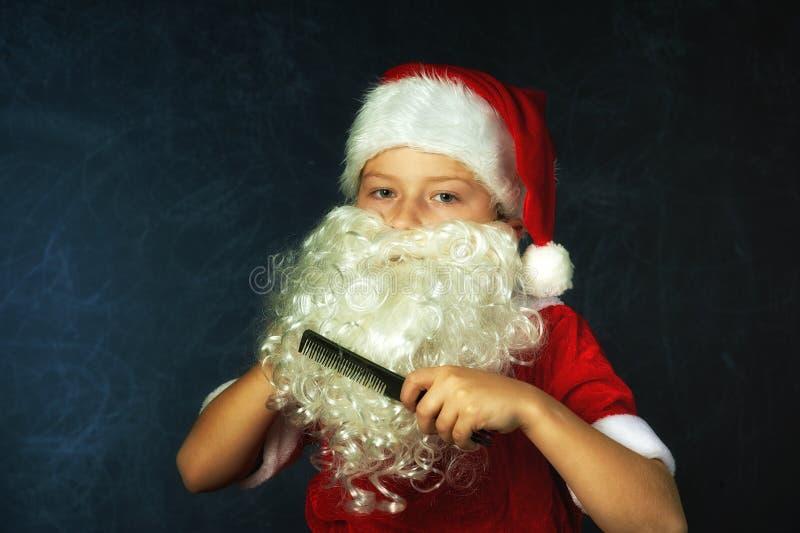 作为圣诞老人项目打扮的男孩的画象 库存照片