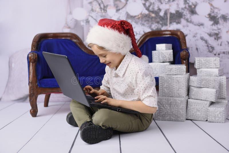 作为圣诞老人项目的一个微笑的男孩与一棵圣诞树在背景中 库存图片