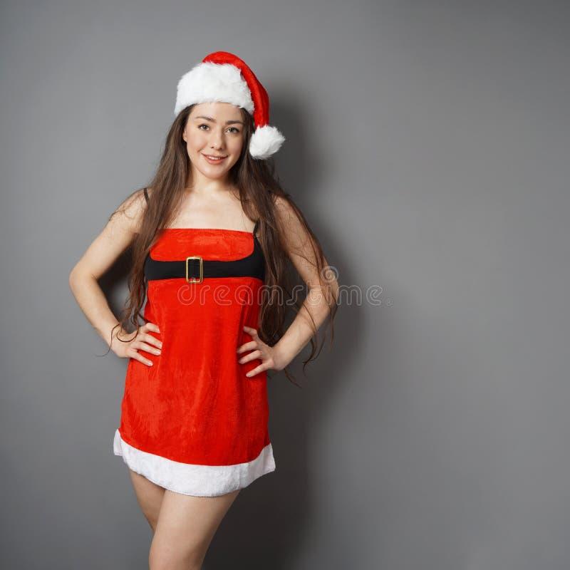 作为在圣诞节服装的错过打扮的年轻女人圣诞老人 免版税图库摄影