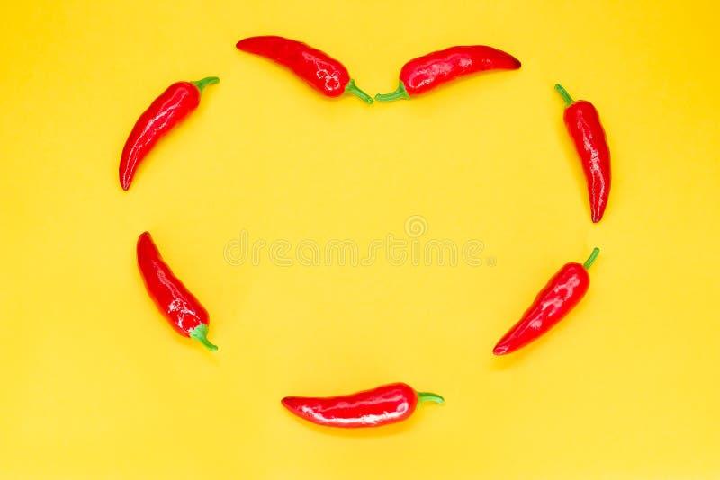作为在白色黄色背景的心脏被塑造的炽热辣椒与拷贝空间 r 免版税图库摄影
