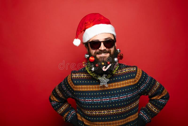 作为在红色背景的圣诞老人打扮的凉快的人 免版税库存图片