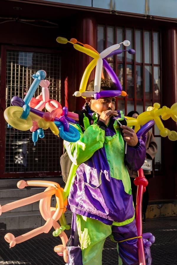 作为小丑打扮的五颜六色的气球卖主 免版税库存照片