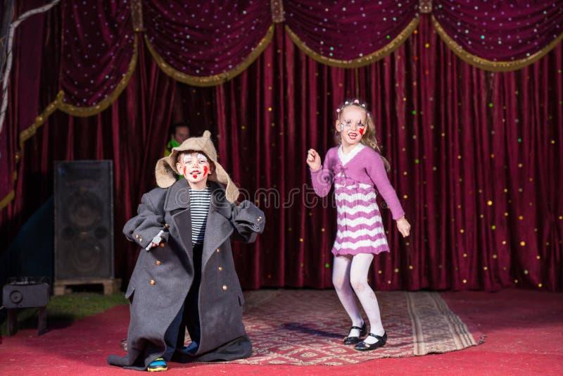 作为小丑打扮的孩子执行在阶段 库存照片