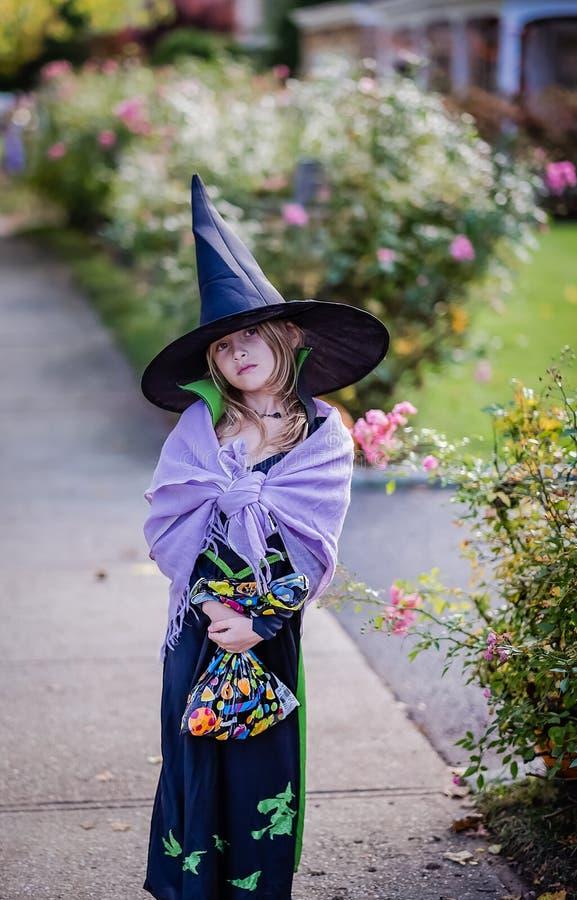 作为巫婆打扮的女孩在万圣夜 免版税库存图片