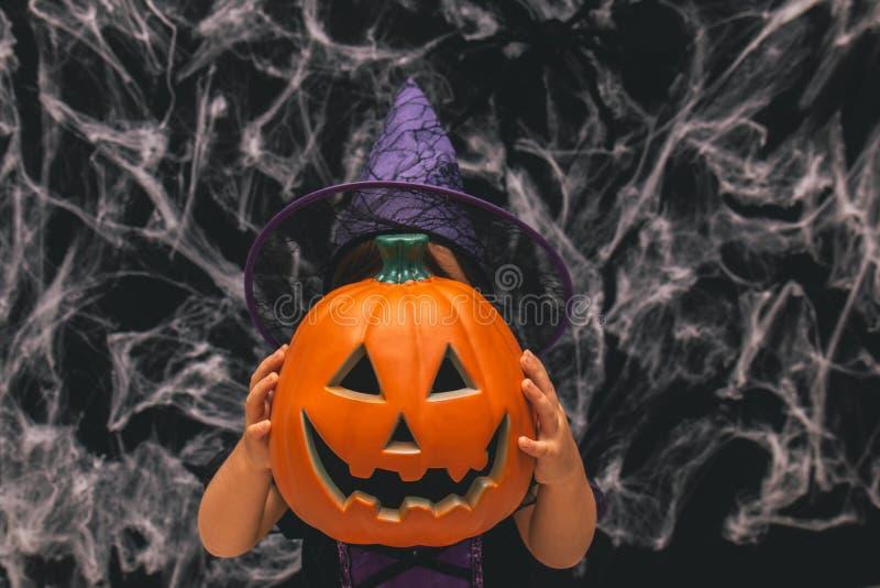 作为巫婆打扮的小女孩拿着南瓜反对与spiderwebs的黑暗的背景 免版税图库摄影