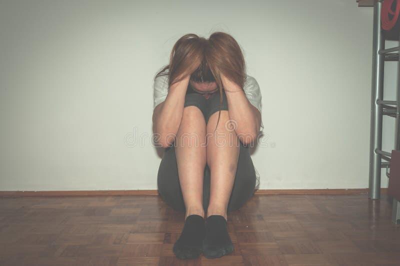 作为年轻人被虐待的沮丧和孤独的女孩单独在她的屋子里坐凄惨地板的感觉和忧虑哀叹她的生活, 图库摄影
