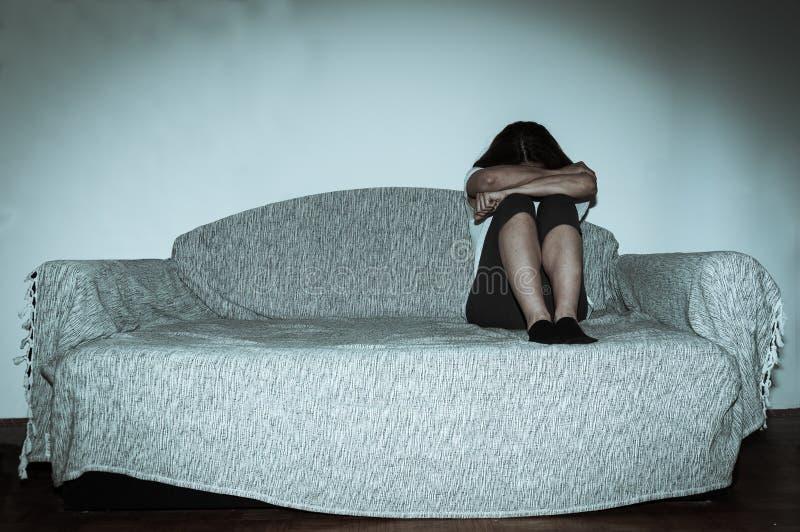 作为年轻感觉被虐待的哭泣的妇女沮丧和凄惨,当单独坐在她的屋子里时的她 库存图片